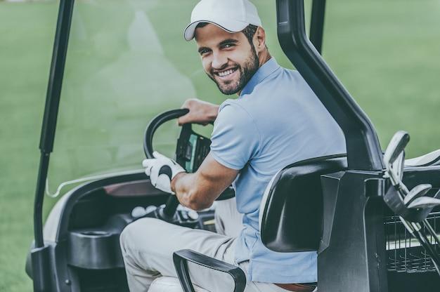На пути к следующей лунке. вид сзади молодого счастливого мужчины-гольфиста, управляющего тележкой для гольфа и смотрящего через плечо
