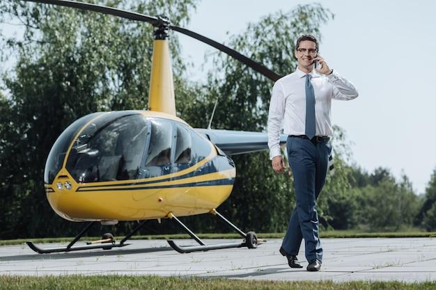 彼の途中。ヘリコプターから離れて歩いている間、彼の電話を使用してヘリポートからタクシーを呼ぶ明るい若いceo