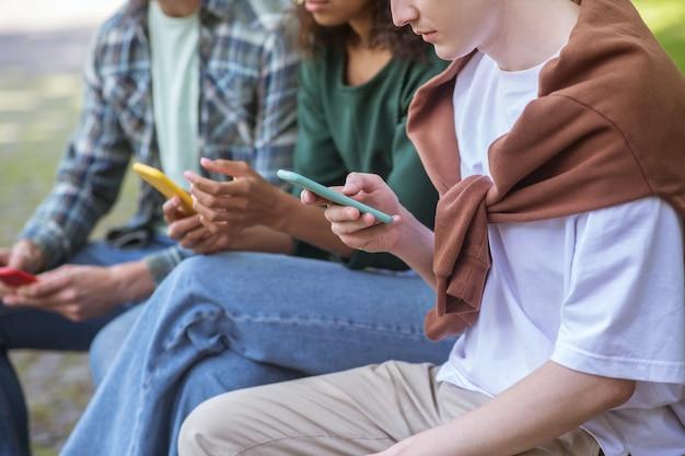 В интернете. группа людей со смартфонами, сидя на скамейке
