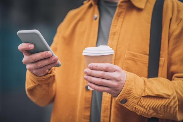 インターネット上で。彼の手に電話を持つオレンジ色のジャケットの男
