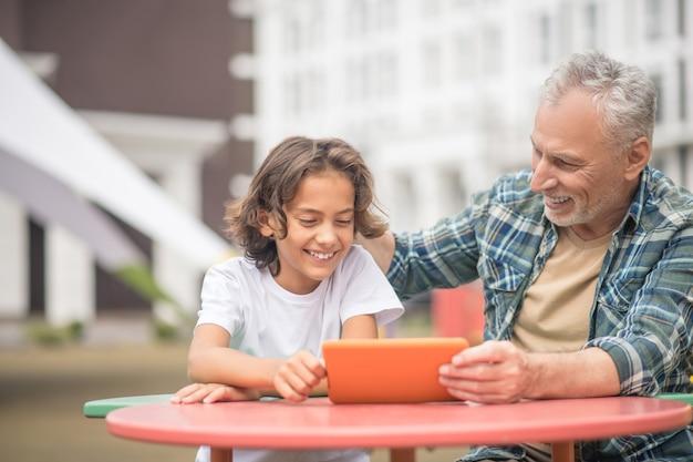 인터넷에서. 아들과 아빠가 태블릿에서 뭔가를보고 관련을 찾고
