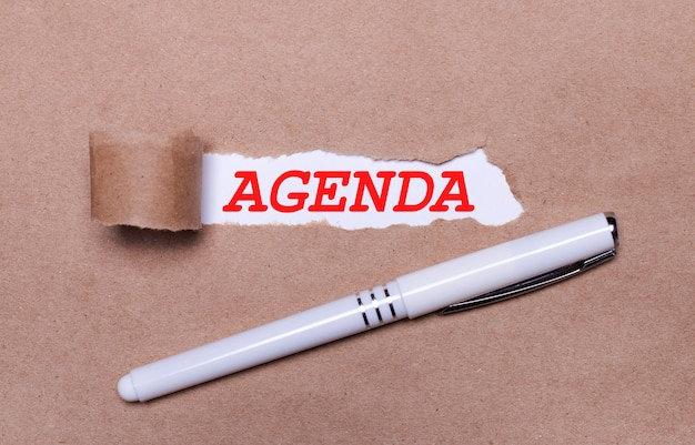 クラフト紙に、白いペンと白い紙片に「agenda」というテキストが付いています。