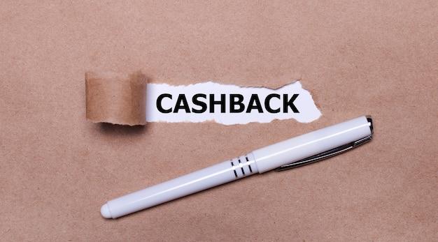 На крафт-бумаге белая ручка и белая полоска бумаги с текстом cashback.