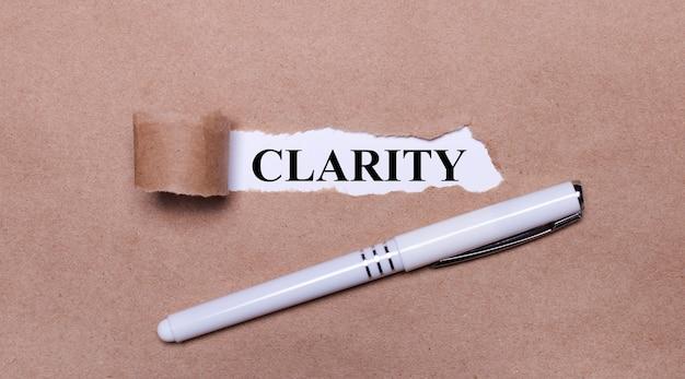 クラフト紙に、白いペンと白い紙片にclarityというテキストが表示されます。