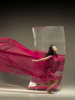 理想への道。鏡付きの茶色の壁にモダンなバレエダンサー。表面での錯覚の反射。柔軟性の魔法、生地による動き。クリエイティブアートダンス、アクション、インスピレーションのコンセプト。