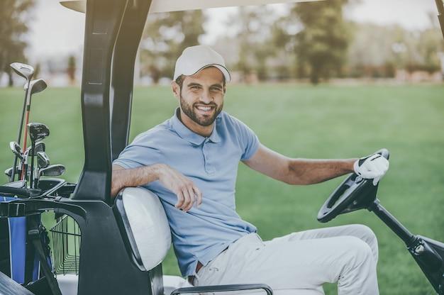 На пути к следующей лунке. вид сбоку на молодого счастливого мужчины-гольфиста, управляющего тележкой для гольфа и смотрящего в камеру