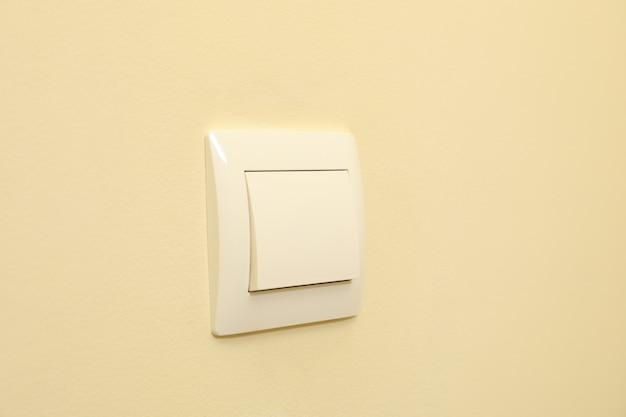 Выключатель света на бежевой стене