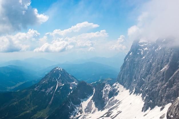 ダッハシュタインの頂上にあり、アルプスの山々を眺めることができます。オーストリア、ヨーロッパの国立公園。夏の日の青く曇り空