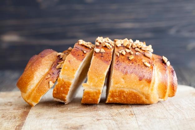 По кусочкам пшеничная булочка сладкая с начинкой и посыпанная жареным арахисом.