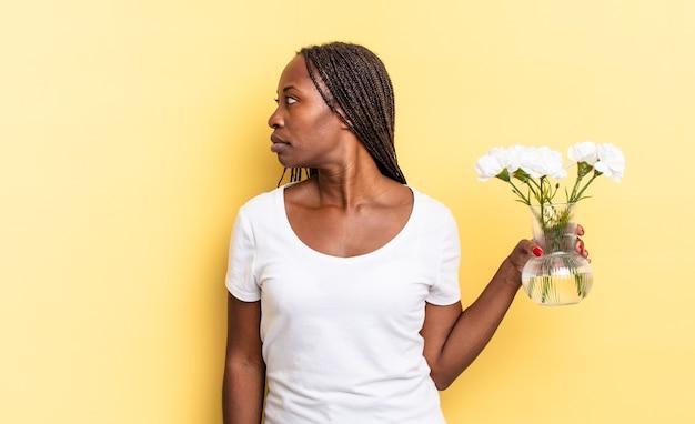 プロフィールビューで、前方のスペースをコピーしようとしている、考えている、想像している、または空想にふけっている。装飾的な花のコンセプト