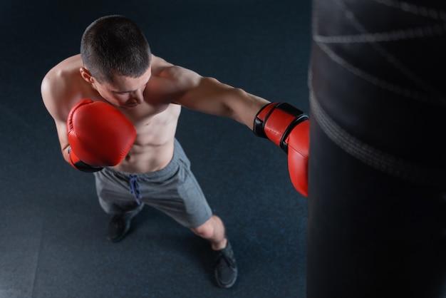 ステロイドについて。サンドバッグで一生懸命働いている間忙しい感じのシャツを着ていないステロイドの運動選手