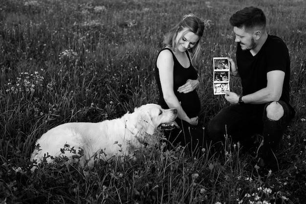 여름 저녁 산책길에 잔디 사이에 앉아 있는 임신한 부부는 태어나지 않은 아이의 래브라도 초음파를 보여줍니다. 흑백 사진. 임신 관리. 현대 검사 방법.