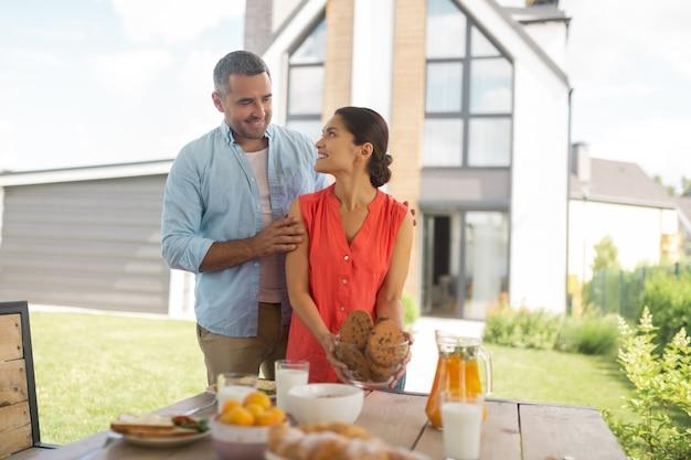 夏のテラスで。夏のテラスのテーブルにクッキーとボウルを置く黒髪の愛情のある妻
