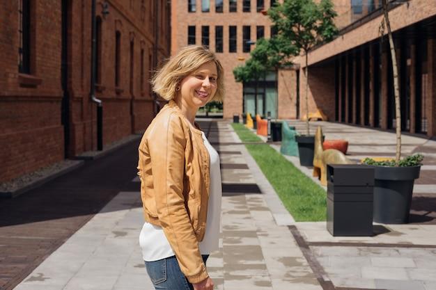 晴れた春の日に、若い女性が素晴らしい気分で街を歩き回るのは素晴らしい観光と喜びです...