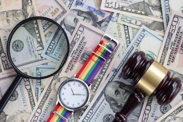 테이블에는 미국 지폐 돋보기 lgbt 시계와 나무 망치가 있습니다. 성 소수자 권리 개념