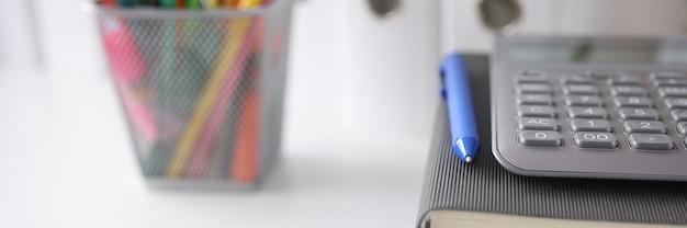На столе лежат документы, дневник, рядом с калькулятором, карандаши, концепция дистанционного обучения.