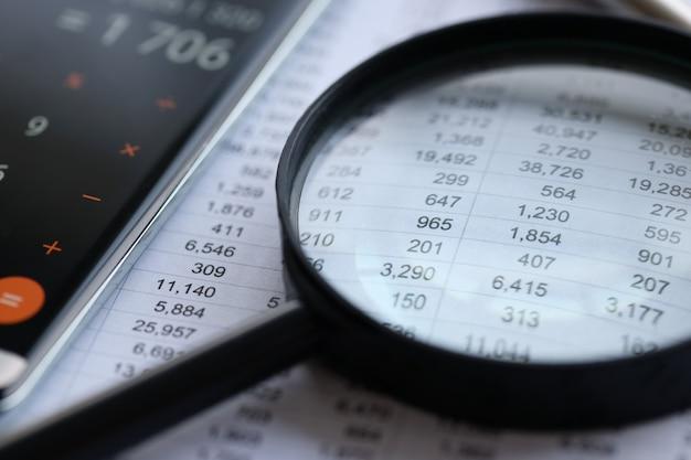 На столе лежат документы с финансовой отчетностью поверх лупы малого и среднего размера.