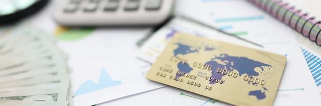 테이블 계산기, 펜, 카드, 문서, 노트북, 돋보기 및 돈.