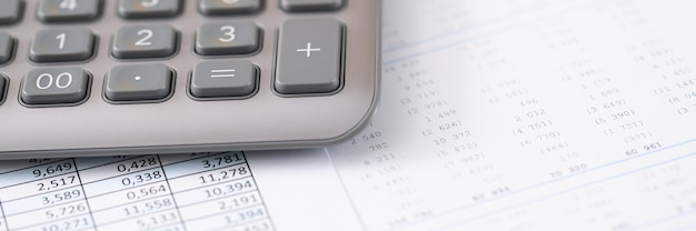 テーブルの上には、財務報告会計サービスの概念を備えた電卓ペンとドキュメントがあります