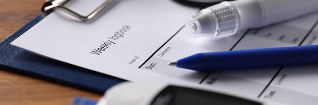 На столе стоит глюкометр и график ежедневного наблюдения сахарный диабет суточный сахар
