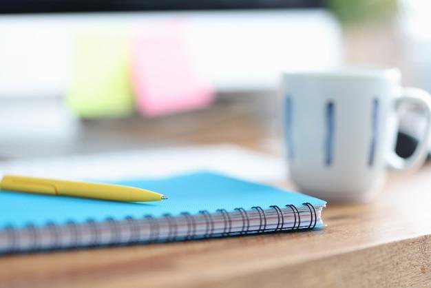 На столе чашка рядом с ручкой и дневник для заметок. концепция дистанционного обучения