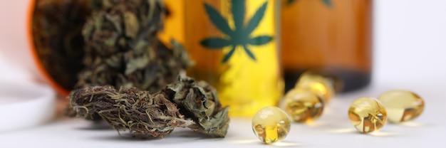 На столе марихуана в банке и конопляное масло в капсулах