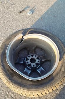 아스팔트 클로즈업에는 알로이 휠이 분리된 자동차의 바퀴가 도로의 구멍에 박혀 있습니다.