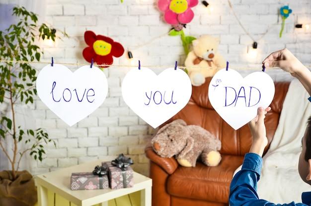 枯れたソファのある区画の背景に、レンガの壁が3本の白いハートの紐に掛けられ、洗濯はさみでステッチされ、子供は碑文を添付します