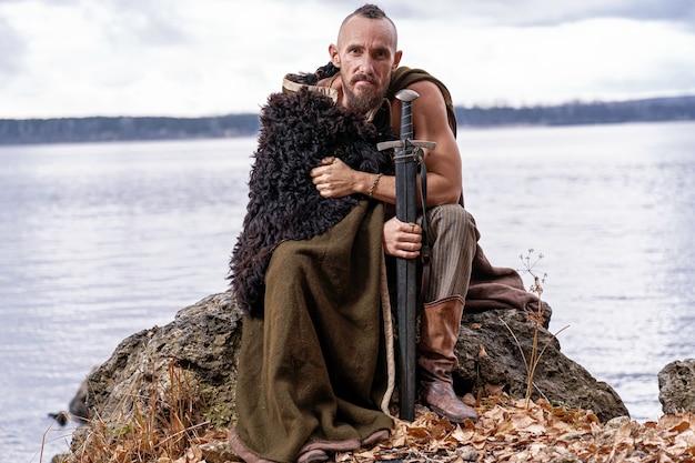 На берегу реки викинг задумчиво сидит на камне с мечом.