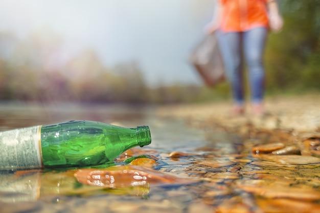 На берегу реки кем-то брошена стеклянная бутылка. на заднем плане - волонтер. концепция защиты окружающей среды и устойчивости. свет.