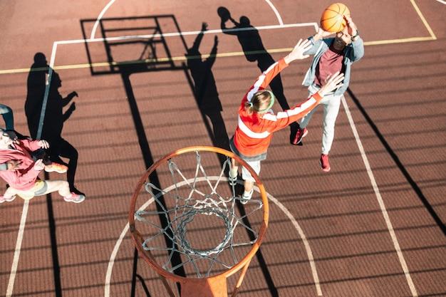 バスケットボールコートで。その下でゲームをしている人々と一緒にスポーツグラウンドの上にぶら下がっているバスケットの上面図