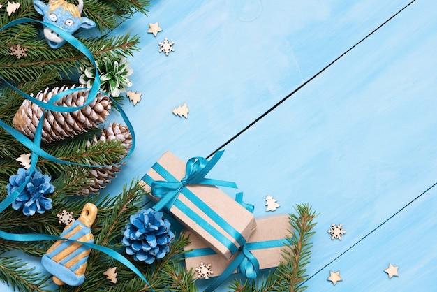青いテーブルには、クリスマスのおもちゃが付いたモミの枝があります。