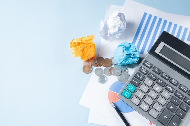 На синем столе калькулятор, статистика, монеты и ручка