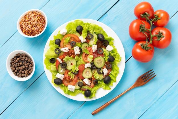 青い木製のテーブルの上には、おいしいギリシャ風サラダのプレートがあります。