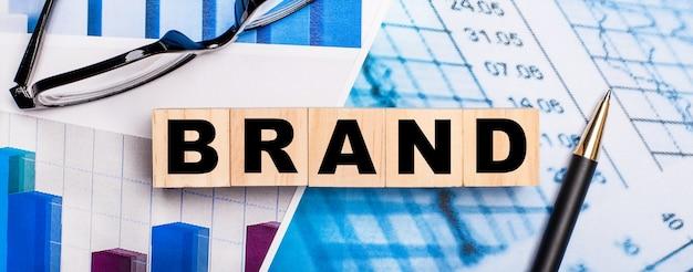 На ярких схемах очки, ручка и деревянные кубики с надписью brand.
