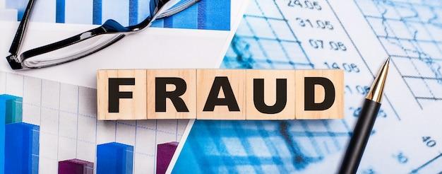 明るい図、眼鏡、ペン、そして詐欺という言葉が書かれた木製の立方体。ビジネスコンセプト