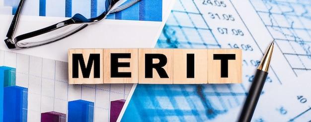 밝은 다이어그램, 안경, 펜 및 merit라는 단어가있는 나무 큐브. 비즈니스 개념