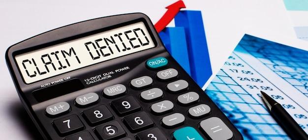 На дисплее калькулятора есть надпись претензия отказана. рядом цветные диаграммы и графики. бизнес-концепция.