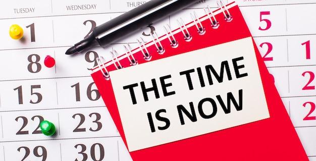 カレンダーには、the time isnowというテキストが書かれた白いカードがあります。近くには赤いメモ帳とマーカーがあります。上から見る