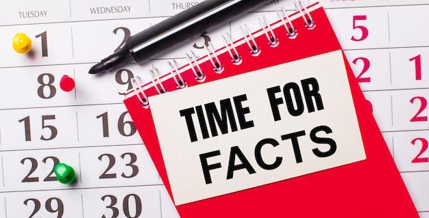 В календаре есть белая карточка с текстом время для фактов. рядом красный блокнот и маркер. вид сверху