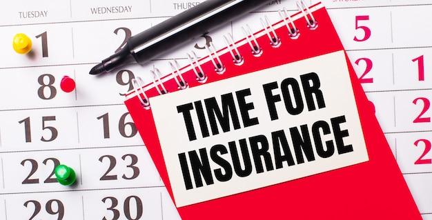 В календаре есть белая карточка с текстом время страховки. рядом красный блокнот и маркер. вид сверху