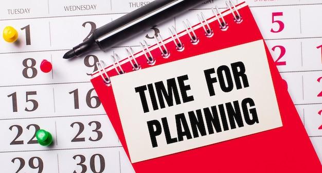 В календаре есть белая карточка с текстом время для планирования. рядом красный блокнот и маркер. вид сверху