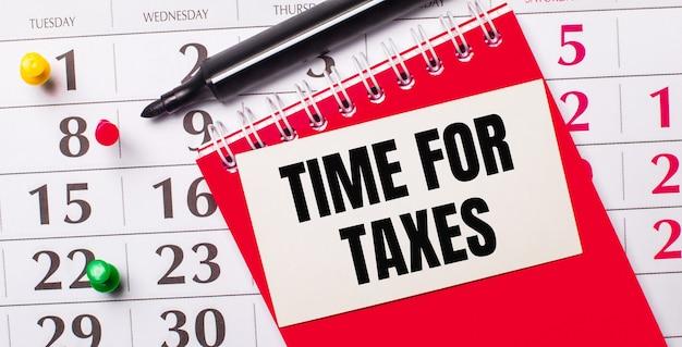 В календаре есть белая карточка с текстом время налогов. рядом красный блокнот и маркер. вид сверху