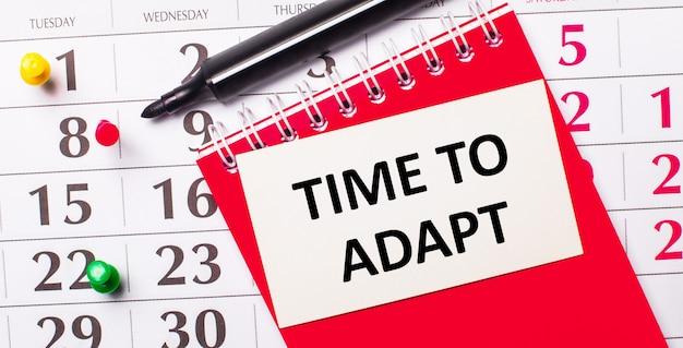 В календаре есть белая карточка с текстом «время адаптировать». рядом красный блокнот и маркер. вид сверху