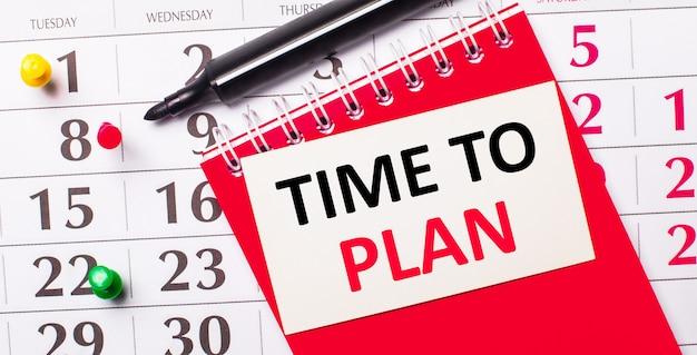 カレンダーには、「計画する時間」というテキストが書かれた白いカードがあります。近くには赤いメモ帳とマーカーがあります。上からの眺め。