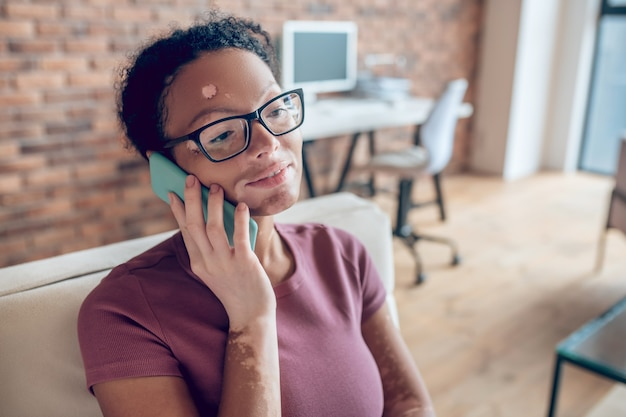 通話中。電話で話し、関与しているように見える眼鏡の女性