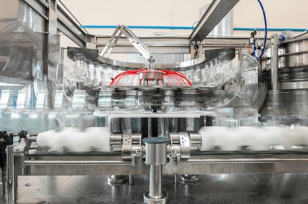 На конвейере стеклянные бутылки. заводской цех по производству стеклянных бутылок и напитков