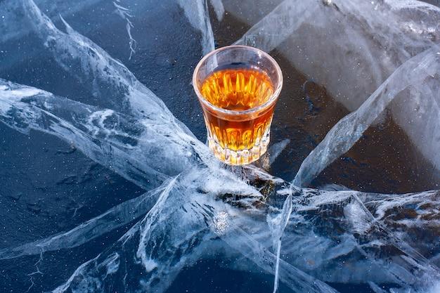 湖のひびの入った氷の上にウイスキーが一杯あります。冷えたウイスキー。美しい深い白い亀裂のある青い氷。側面からの上面図。アルコール製品の宣伝。水平。