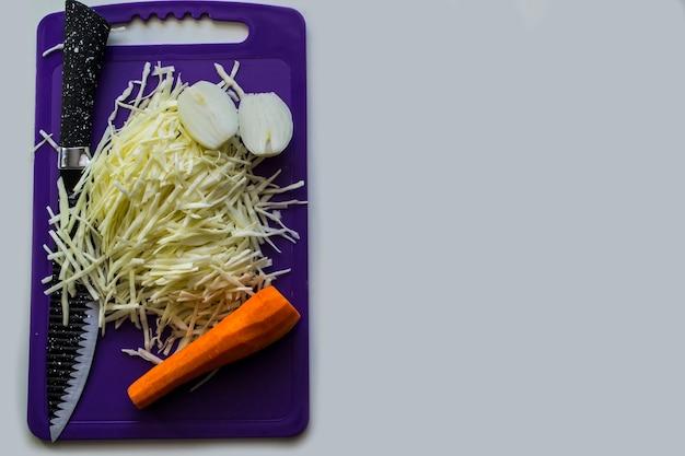 흰색 바탕에 칼을 든 도마 위에 야채
