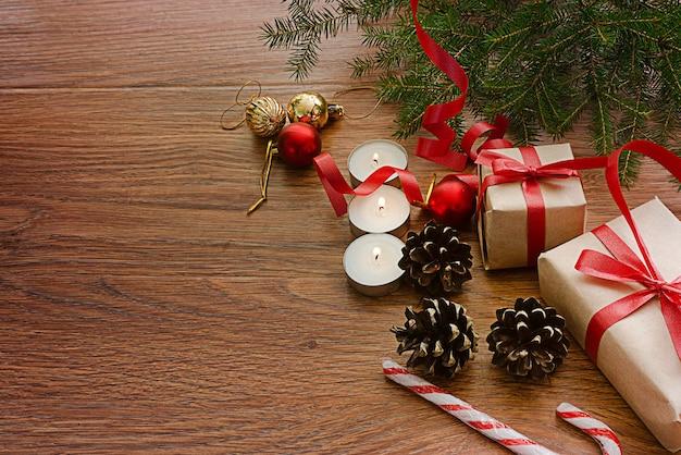 右側の暗い背景には、トウヒの枝、クリスマスのおもちゃ、ギフト、キャンドル、コーンがあります。